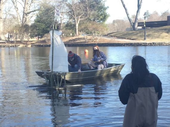 Students in the Public Art class assist by untangling the wires of a bamboo boat