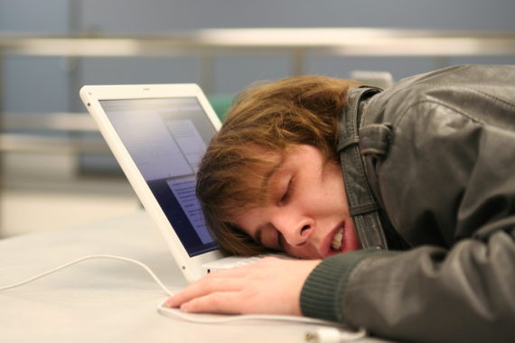 College student asleep on his computer